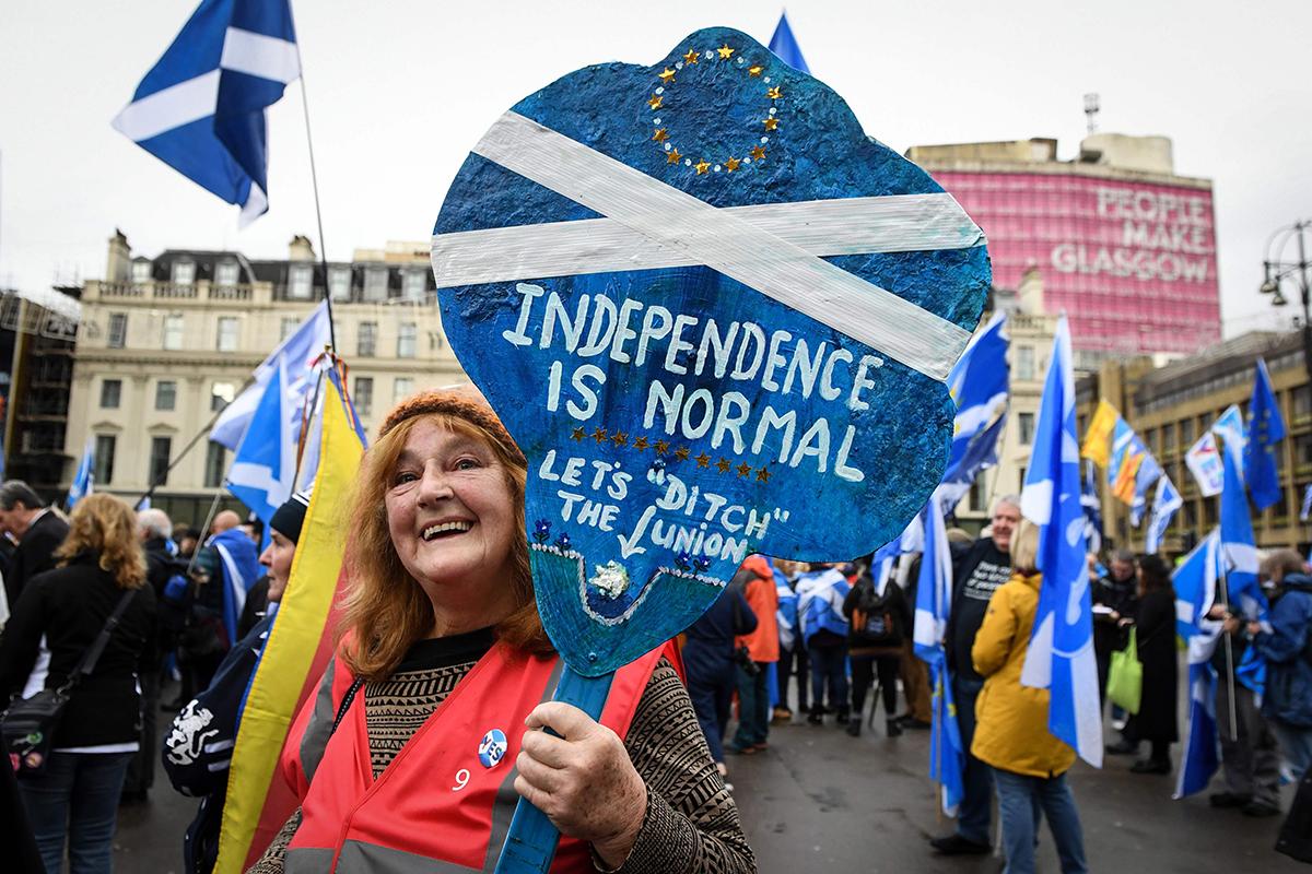 """Bilde som viser en dame i en demonstrasjon i Glasgow med en fane som sier """"Independence is normal""""."""