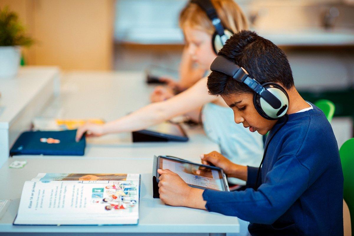 Elever arbeider med bok og nettbrett