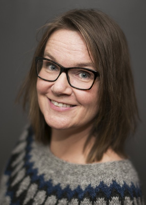 Forfatter Lise Forfang Grimnes ser skrått opp og inn i kameraet og smiler
