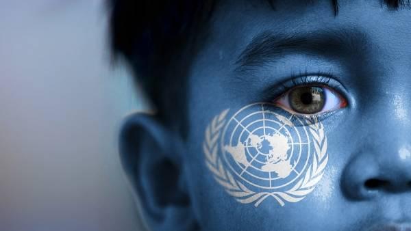 fargebilde i blåtoner, viser en kvart av en gutts ansikt med øyne og nese med FN-symbolet som lyser opp kinnet hans