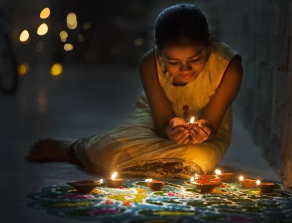 Jente som sitter med et lys i hånden og noen lys og en rangoli foran seg. Lys kjole og mørkt hår i hestehale. Bakgrunnen er mørk