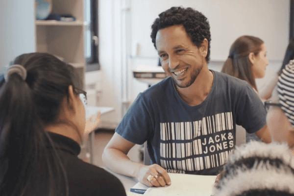 Bildet viser en smilende deltaker vendt mot to andre i et gruppearbeid