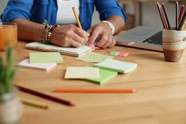 Bilde av post-it lapper, mac og to hender som noterer