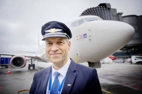 Pilot Espen står på bakken foran flyet og smiler.