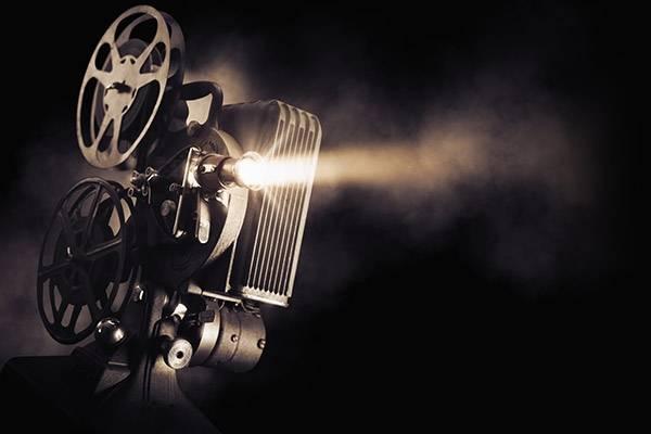 Filmprojektor mot mørk bakgrunn med lysstråle.