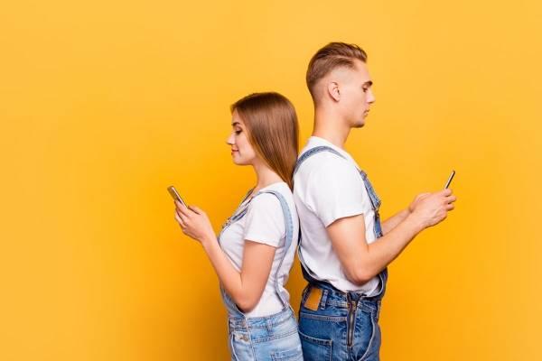 Jente og gutt holder hver sin mobil