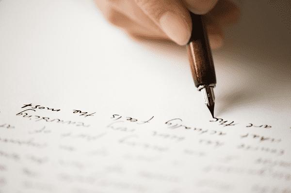 Bildet viser spissen av en fyllepenn som skriver med blekk på papiret