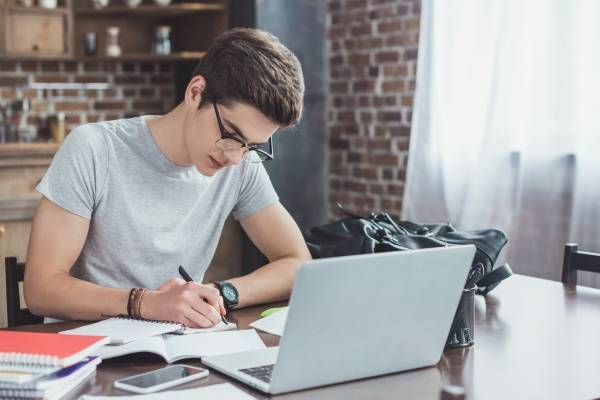 En gutt gjør lekser hjemme.