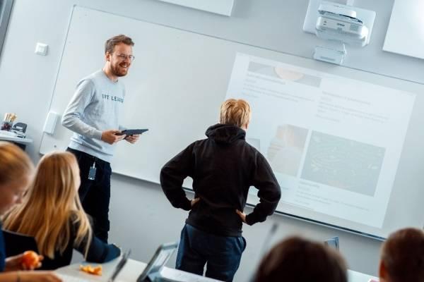Lærer og elev står ved en smarttavle i klasserommet