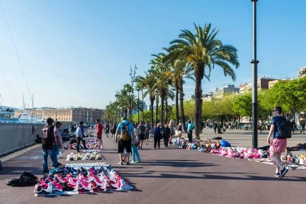 Langs med en havnepromenade har flere gateselgere spredd ut varene sine. I forkant av bildet står det en mann med mange rosa og hvite sko foran seg. Bak han står det en mann med mange hatter foran seg og videre bak dem står det mange andre som den med ulike varer. Mennesker spaserer bortover promenaden. På høyre side av bildet er det en rad med palmer. Himmelen er lyseblå.