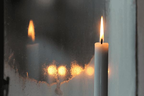 Bildet viser et stearinlys som brenner mot et vindu som dugger