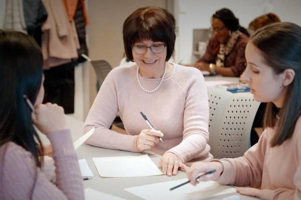 Bildet viser lærer og to elever i en Aktivt klasserom-situasjon der de diskuterer et tema med penn og papir foran seg.
