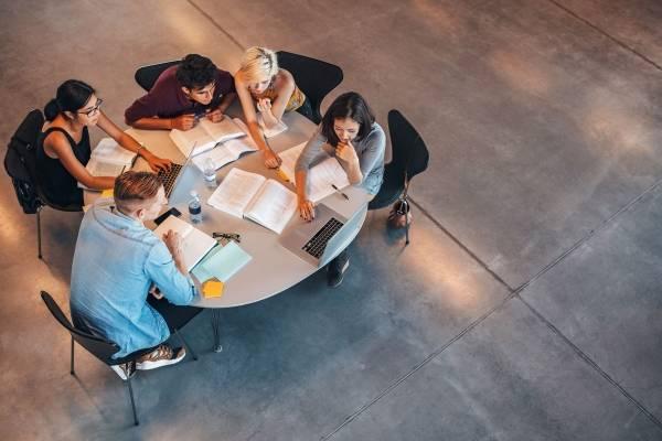 Elever sitter rundt et bord og leser sammen