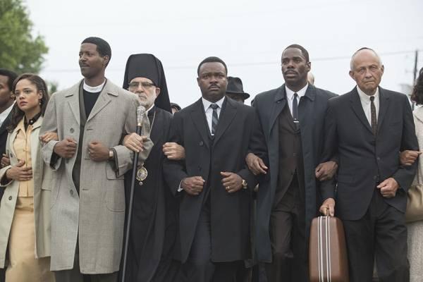 Filmbilde: En gruppe menn og kvinner går arm i arm og danner en fast rekke.