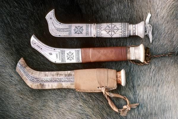 Bildet viser tre samekniver i typiske slirer med mønstre oppå et reinsdyrskinn