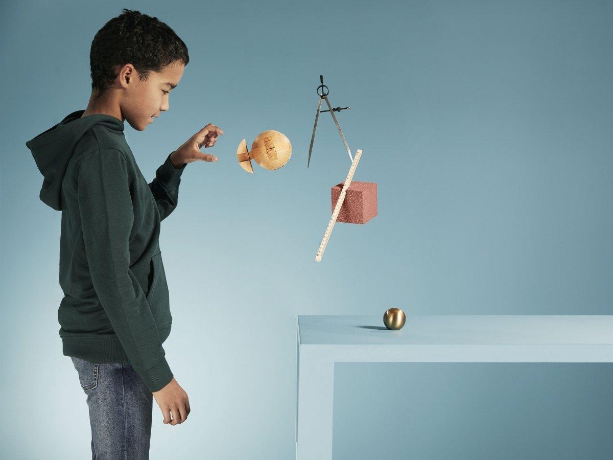 Illustrasjonsfoto av gutt som utforsker ulike elementer. Noen av elementene svever i lufta, mens andre ligger på et bord.